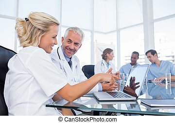 Two smiling doctors looking at a laptop in office