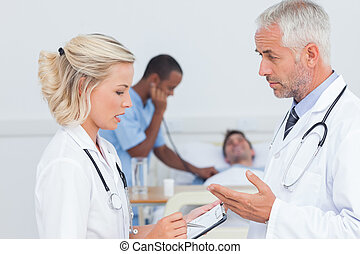 Doctors speaking together about the patient in front of him