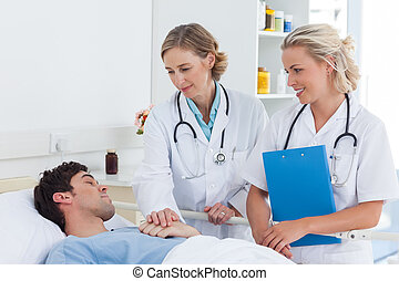 Two women doctors taking care of a patient