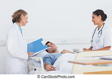 Doctors explaining the symptoms to a patient in a hospital