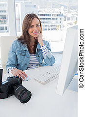 Smiling photographer editing at desk on computer in modern...