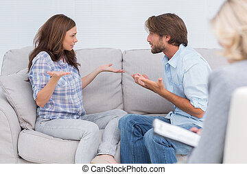 Couple going through therapy and crying on the couch as...