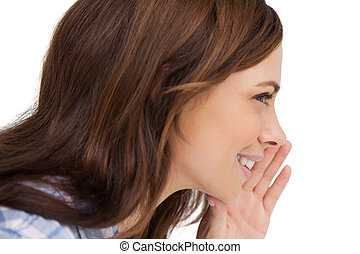 Brunette woman whispering a secret on white background