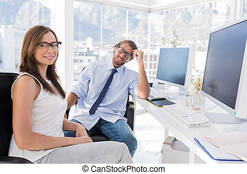 Designers sitting at their desk and smiling