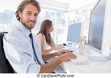 Attractive designer at work with colleague behind him