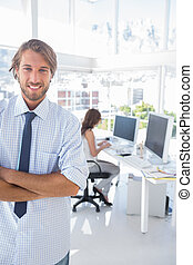 Smiling designer standing in office with arms crossed and...