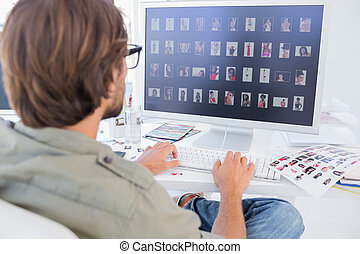 Photo editor viewing thumbnails on computer at his desk