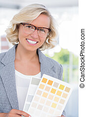 Beautiful interior designer holding up colour samples in...