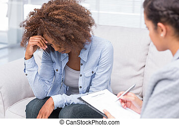 Woman sitting on sofa and crying in therapy - Woman sitting...