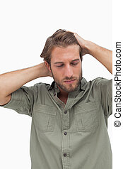 Stressed man looking down with hands on head on white...