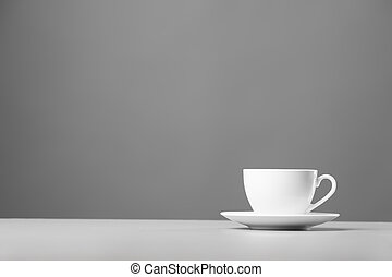 White mug on a gray background. - White mug and saucer on a...