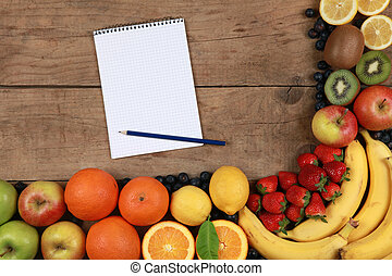 Fruits on a wooden board with notebook