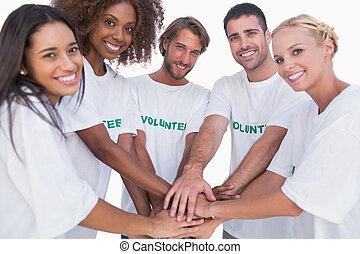 sonriente, voluntario, grupo, poniendo, Manos, juntos