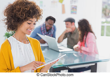 Editor using tablet and smiling as team works behind her at...
