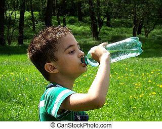 Tired child drinks water on a sunny day