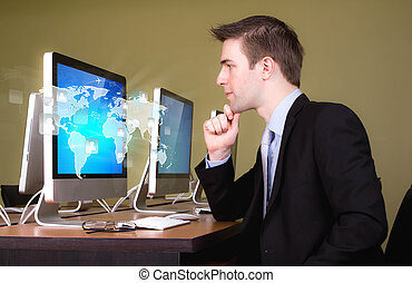 Portrait of young business man working in computer room with...
