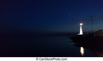 Lighthouse on the water edge near sea at night, timelapse
