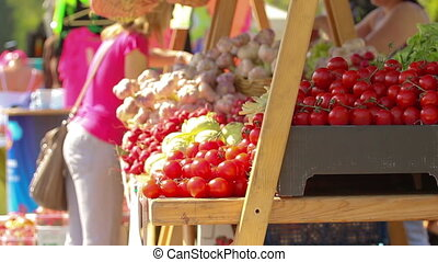 Food stand selling tomatoes, garlic and other vegetables on...