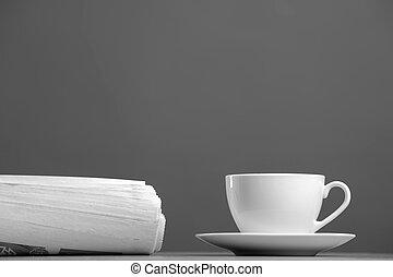White mug and newspaper on a gray background
