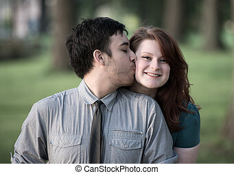 Loving young man kissing his girlfriend