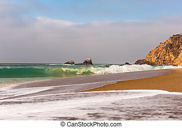 Beach and waves - Waves breaking along the shoreline of a...
