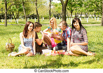 Group of students enjoying a summer picnic sitting together...