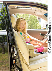 Young attractive blond girl seated a car