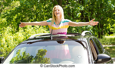 Playful woman standing in a car sunroof - Playful vivacious...