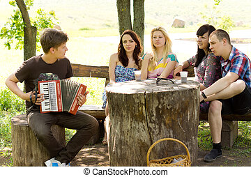 Young man playing music for his friends on an accordion as...