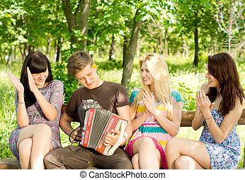 Friends enjoying music played on a concertina - Three...