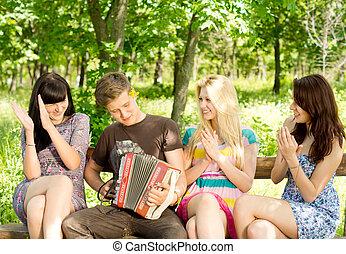 Friends enjoying music played on a concertina - Three...