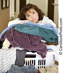 woman resting on pile of laundry - Unhappy, sad, tired woman...