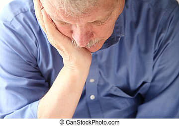 older man slumped in depression - unhappy senior man...