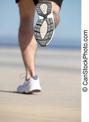 Back view of an unfocused legs of a man running on the...