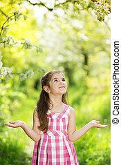 Cute girl - Cute little girl is holding flower outside in...