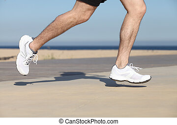 Side view of a man legs running on the concrete of a seafront