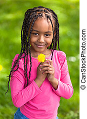 Outdoor portrait of a cute young black girl - African people...
