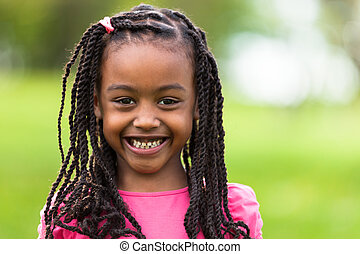 Outdoor close up portrait of a cute young black girl smiling...