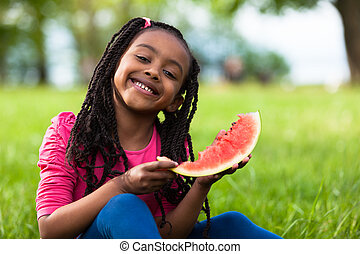 Outdoor portrait of a cute young black little girl eating...