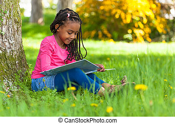 Outdoor portrait of a cute young black little girl reading a...