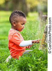 Outdoor portrait of a cute young little black boy playing...