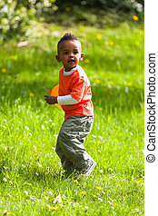 Outdoor portrait of a cute young  little black boy playing with a balloon - African people