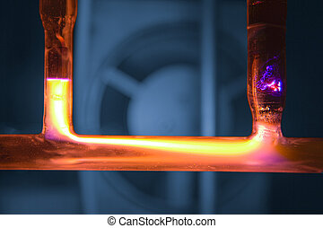 Yellow plasma discharge in tube, blue background with...