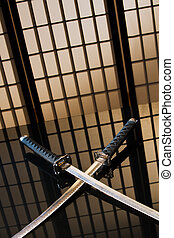 Katana and wakizashi with naked blades on a table in yellow...