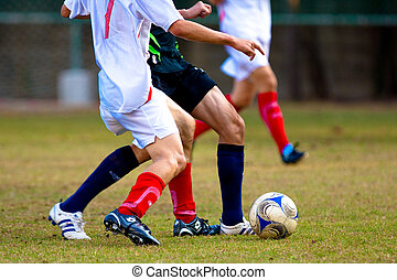 Soccer players fighting for ball. Shot outdoor.