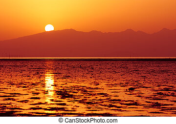 Sun is setting down above sea waters and hills - Sun is...