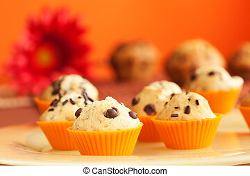 Vanilla muffins with chocolate chips in orange cups