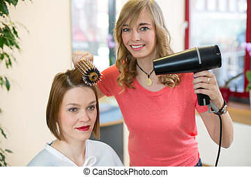 hairdresser making locks with barrel brush and blow-dryer -...