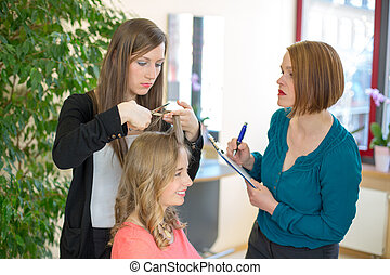 Apprentice cutting hair while instructor is watching -...