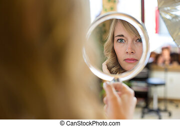 Client in hairdresser salon watches herself in mirror -...